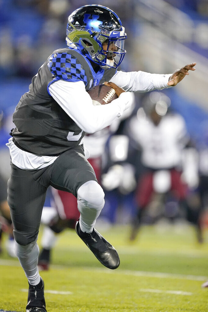 Kentucky quarterback Terry Wilson scrambles with the ball during the first half of an NCAA college football game against South Carolina, Saturday, Dec. 5, 2020, in Lexington, Ky. (AP Photo/Bryan Woolston)