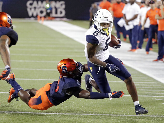 West Virginia running back Kennedy McKoy (6) is tackled by Syracuse defensive back Evan Foster after gaining yardage during the first half of the Camping World Bowl NCAA college football game Friday, Dec. 28, 2018, in Orlando, Fla. (AP Photo/John Raoux)