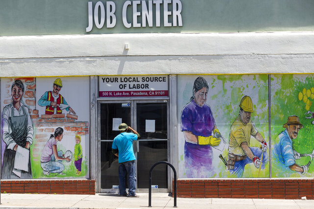 FILE - In this May 7, 2020 file photo, a person looks inside the closed doors of the Pasadena Community Job Center in Pasadena, Calif., during the coronavirus outbreak. California's unemployment rate continued to climb in May, reaching 16.3% as businesses continued to lay people off because of a state-at-home order aimed at slowing the spread of the coronavirus that has wrecked the state's economy.  (AP Photo/Damian Dovarganes, File)
