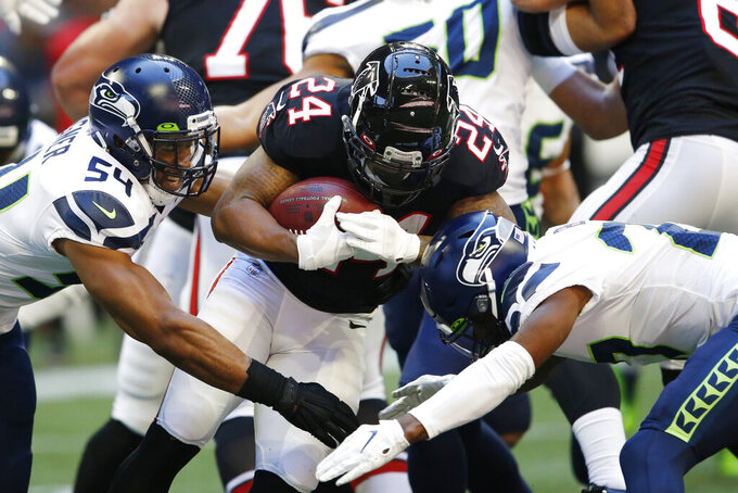 Atlanta Falcons running back Devonta Freeman (24) runs into Seattle Seahawks middle linebacker Bobby Wagner (54) during the first half of an NFL football game, Sunday, Oct. 27, 2019, in Atlanta. (AP Photo/John Bazemore)