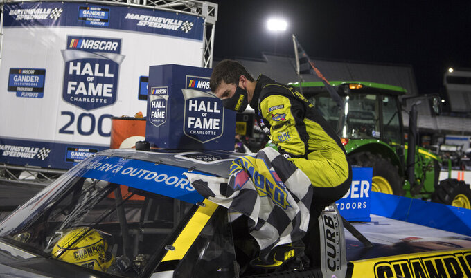 Grant Enfinger climbs from his vehicle after winning the NASCAR Truck Series auto race at Martinsville Speedway in Martinsville, Va., Friday, Oct. 30, 2020. (AP Photo/Lee Luther Jr.)