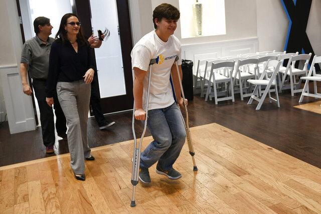 In this May 14, 2019, photo shooting victim Josh Jones, arrives on crutches with his parents David, in back, and Lorie, left, before speaking to the media for the first time since the shooting at STEM school in Littleton, Colo. Jones along with fellow student Brendan Bialy helped disarm one of two gunmen that entered their school killing their classmate Kendrick Castillo and wounding others. Faith and a newfound sense of purpose have helped Jones cope over the past year, even as he ponders — without answers — why he and his friends have had to deal with this tragedy at their age and how others don't have to know what it feels like. (Helen H. Richardson/The Denver Post via AP)