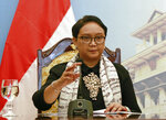 Indonesian Foreign Minister Retno Marsudi adjusts the microphone during a briefing with her Vietnamese counterpart Pham Binh Minh in Hanoi, Vietnam, Tuesday, April 17, 2018. The two countries pledge to work together to resolve the fishing violations in the South China Sea as the they seek to boost their bilateral trade. (AP Photo/Tran Van Minh)