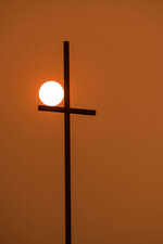 In a sky with wildfire smoke, the rising sun shines orange behind a church's cross in Walla Walla, Wash., Wednesday, Sept. 16, 2020. (Greg Lehman/Walla Walla Union-Bulletin via AP)