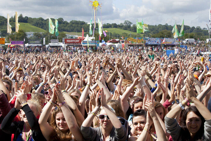 FILE - In this Friday, June 24, 2011 file photo, the crowd at Glastonbury Music Festival clap their hands above their heads as they watch Chipmunk on stage, Glastonbury, England. Britain's Glastonbury music festival has fallen victim to the coronavirus pandemic for the second year in a row, organizers Michael Eavis and Emily Eavis said Thursday Jan. 21, 2021. (AP Photo/Joel Ryan, File)