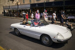 Tourists wearing face masks look on as a classic sports car drives through the Saint-Tropez port in southern France, Saturday Aug 8, 2020. The glamorous French Riviera resort of Saint-Tropez is requiring face masks outdoors starting Saturday, threatening to sober the mood in a place renowned for high-end, free-wheeling summer beach parties. (AP Photo/Daniel Cole)