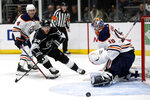 Edmonton Oilers goaltender Mikko Koskinen, right, of Finland, deflects a shot by Los Angeles Kings left wing Dustin Brown, center, with Oilers defenseman Kris Russell, left, defending during the second period of an NHL hockey game in Los Angeles, Thursday, Nov. 21, 2019. (AP Photo/Alex Gallardo)