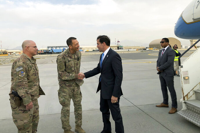 U.S. Defense Secretary Mark Esper, center, is greeted by U.S. military personnel upon arriving in Kabul, Afghanistan, Sunday, Oct. 20, 2019. Esper arrived Sunday in Afghanistan, where stalled peace talks with the Taliban and persistent violent attacks by the insurgent group and Islamic State militants have complicated the Trump administration's pledge to withdraw more than 5,000 American troops. He told reporters traveling with him that he believes the U.S. can reduce its force in Afghanistan without hurting the counterterrorism fight against al-Qaida and the Islamic State group. (AP Photo/Lolita C. Balbor)