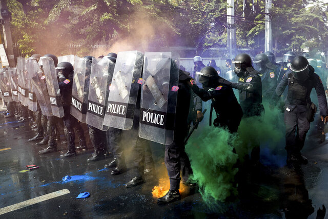Riot police stand in formation as pro-democracy protesters throw smoke bombs near the Parliament in Bangkok, Tuesday, Nov. 17, 2020. Thailand's political battleground shifted to the country's Parliament Tuesday, where lawmakers are considering proposals to amend the country's constitution, one of the core demands of the student-led pro-democracy movement. (AP Photo/Wason Wanichakorn)