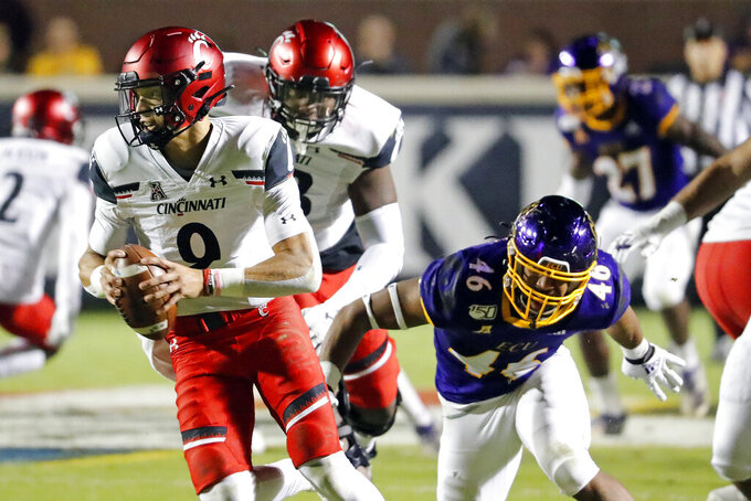 Cincinnati's Desmond Ridder (9) avoids a rush by East Carolina's Chance Purvis (46) during the first half of an NCAA college football game in Greenville, N.C., Saturday, Nov. 2, 2019. (AP Photo/Karl B DeBlaker)