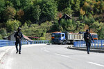 Kosovo police officers patrol the bridge over Gazivode lake near the northern Kosovo border crossing of Brnjak on the fifth day of protest on Friday, Sept. 24, 2021. Ethnic Serbs in Kosovo have been blocking the border for a fifth straight day to protest a decision by Kosovo authorities to start removing Serbian license plates from cars entering the country, raising fears such incidents could unleash much deeper tensions between the two Balkan foes.(AP Photo/Visar Kryeziu)