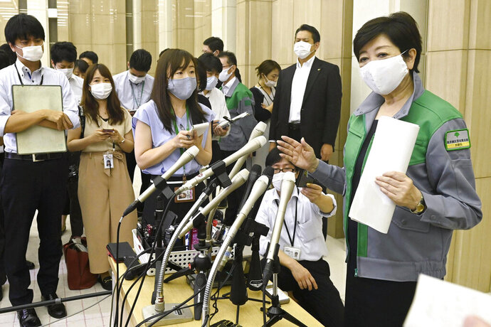 """Tokyo Governor Yuriko Koike, right, speaks to media at the Metropolitan Government Office Thursday, July 9, 2020, in Tokyo. Tokyo confirmed more than 220 new cases Thursday, exceeding its record daily increase from mid-April and prompting concerns of widening of the infections. Tokyo's more than 7,000 cases are about one-third of Japan's total. """"It's a wake-up call,"""" Gov. Koike told reporters. """"We need to use extra caution against the further spread of the infections.""""(Kyodo News via AP)"""