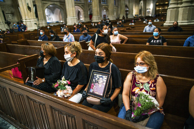 Mourners hold images of loved one during the blessing of cremated remains of Mexicans who died from COVID-19 at St. Patrick's Cathedral, Saturday, July 11, 2020, in New York. The ashes were blessed before they were repatriated to Mexico. (AP Photo/Eduardo Munoz Alvarez)