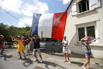 People wave as they wait for the riders to pass during the fifth stage of the Tour de France cycling race over 204.5 kilometers (127 miles) with start in Lorient and finish in Quimper, France, Wednesday, July 11, 2018. (AP Photo/Christophe Ena )