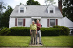 In this Saturday, July 17, 2021, photo, Fred Ware, left, stands outside his home with his son Dave Ware in Manchester, Conn. Fred and Dave Ware recently found a whites-only covenant on his property dating back to 1942 when researching the title chain. Upon finding the covenant, Dave Ware, who grew up in the home, reached out to state lawmakers and helped get a bill passed that strips these covenants on properties. (AP Photo/Jessica Hill)