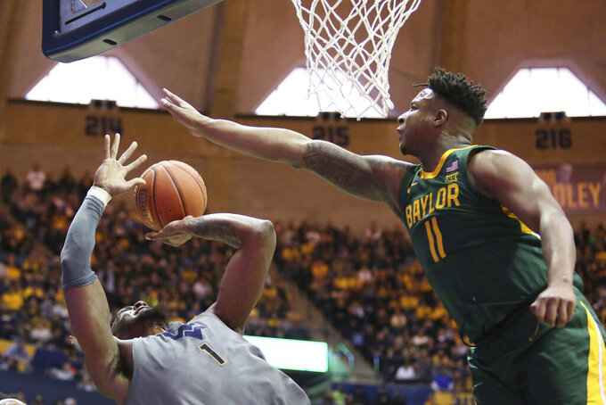 West Virginia forward Derek Culver (1) shoots as Baylor guard Mark Vital (11) defends during the second half of an NCAA college basketball game Saturday, March 7, 2020, in Morgantown, W.Va. (AP Photo/Kathleen Batten)
