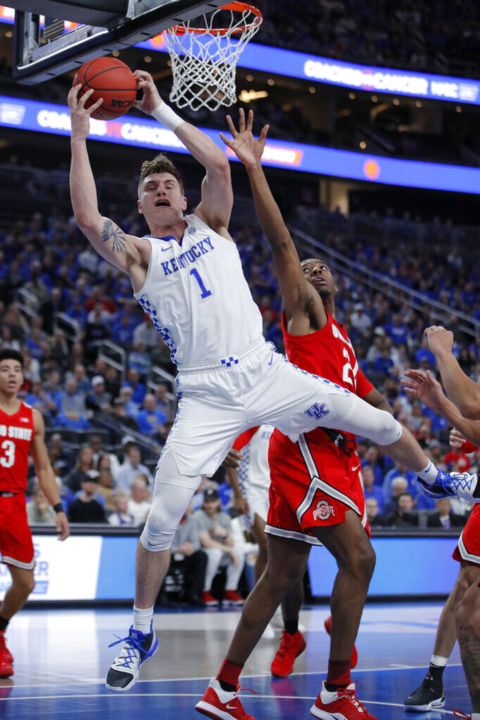 Kentucky's Nate Sestina (1) grabs a rebound around Ohio State's Andre Wesson (24) during the first half of an NCAA college basketball game Saturday, Dec. 21, 2019, in Las Vegas. (AP Photo/John Locher)