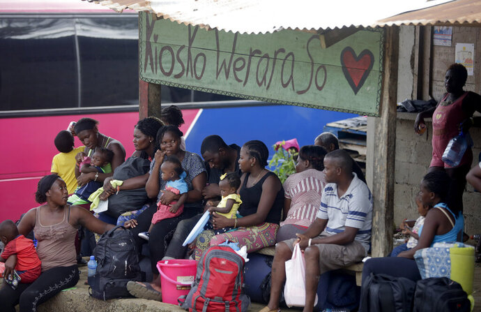 In this May 10, 2019, photo, a group of migrants wait for buses to take them north, in Peñitas, Darien province, Panama. Panamanian authorities are struggling to contend with a spike in the number of migrants risking the journey through what's known as the Darien Gap, a roadless, lawless stretch of tropical isthmus that's one of the most dangerous stretches for people heading north from South America, usually toward the United States or Canada. (AP Photo/Arnulfo Franco)