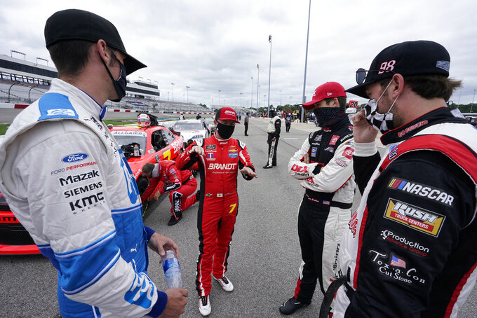 Winner of last night's Xfinity race Justin Allgaier, center, talks with Austin Cindric, left, Chase Briscoe, right, and Harrison Burton, second from right, prior to the start of a NASCAR Xfinity Series auto race Saturday, Sept. 1, 2020, in Richmond, Va. (AP Photo/Steve Helber)