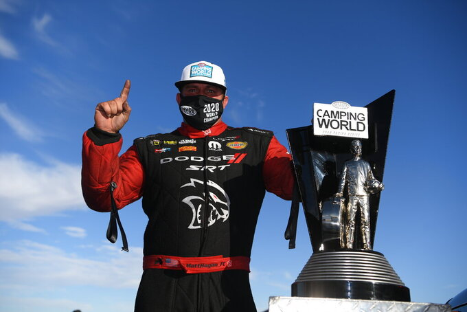 In this photo provided by the NHRA, Funny Car's Matt Hagan scored his third world title at Dodge NHRA Finals presented by Pennzoil and went on to win the event over teammate Ron Capps thanks to his 3.914-second pass at 326.40 mph, Sunday, Nov. 1, 2020, in Las Vegas.  (Jerry Foss/NHRA via AP)