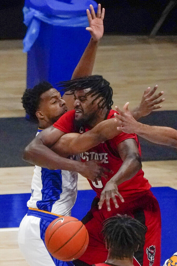 North Carolina State's DJ Funderburk, right, gets tangles with Pittsburgh's Xavier Johnson as he tries to pass during the first half of an NCAA college basketball game, Wednesday, Feb. 17, 2021, in Pittsburgh. (AP Photo/Keith Srakocic)