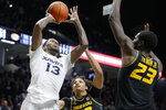 Xavier's Naji Marshall (13) shoots next to Missouri's Jeremiah Tilmon (23) during overtime of an NCAA college basketball game Tuesday, Nov. 12, 2019, in Cincinnati. (AP Photo/John Minchillo)
