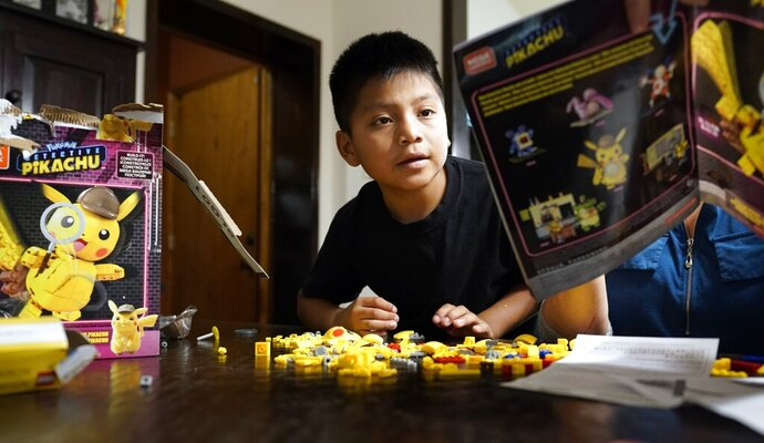 FILE - In this June 24, 2019, file photo, Byron Xol, an immigrant from Guatemala, builds a Lego set in Buda, Texas. Byron was separated from his father, David Xol-Cholom, in May 2018, during the Trump administration's wide-scale separation of immigrant families. A federal judge has ordered the U.S. government to allow the return of 11 parents who were deported without their children during the Trump administration's wide-scale separation of immigrant families. (AP Photo/David J. Phillip, File)