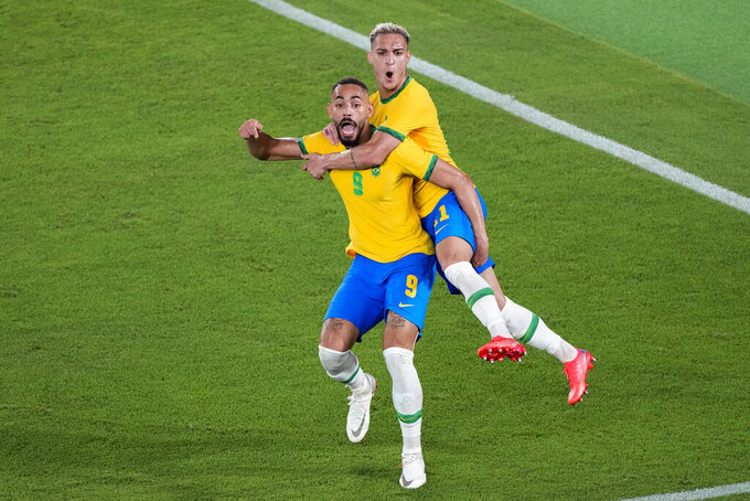 Brazil's Antony embraces teammate Matheus Cunha after he scored his side's opening goal against Spain in the men's soccer final match at the 2020 Summer Olympics, Saturday, Aug. 7, 2021, in Yokohama, Japan. (AP Photo/Martin Mejia)