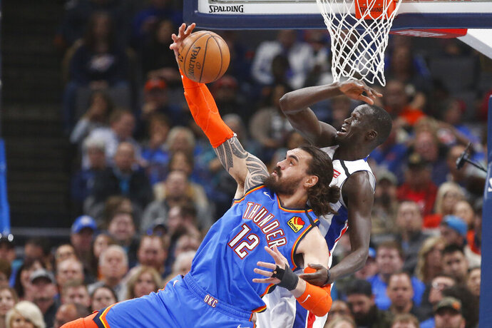 Oklahoma City Thunder center Steven Adams (12) reaches for a pass in front of Detroit Pistons forward Thon Maker, right, during the first half of an NBA basketball game Friday, Feb. 7, 2020, in Oklahoma City. (AP Photo/Sue Ogrocki)
