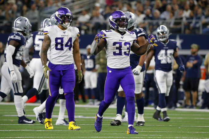 Minnesota Vikings running back Dalvin Cook (33) celebrates his carry for a first down, next to Irv Smith (84) during the second half of the team's NFL football game against the Dallas Cowboys in Arlington, Texas, Sunday, Nov. 10, 2019. (AP Photo/Michael Ainsworth)