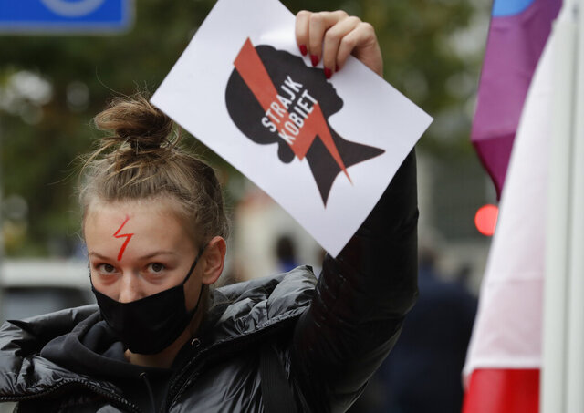 A women's rights activist with a poster of the Women's Strike action protests in Warsaw, Poland, Wednesday, Oct. 28, 2020 against recent tightening of Poland's restrictive abortion law. Massive nationwide protests have been held ever since a top court ruled Thursday that abortions due to fetal congenital defects are unconstitutional. (AP Photo/Czarek Sokolowski)