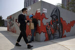A man lowers his mask to smoke as he walks past graffiti artwork in Beijing Monday, July 13, 2020. China reported eight new cases, all of them brought from outside the country, as domestic community infections fall to near zero (AP Photo/Ng Han Guan)