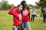 Wearing a Working Families Party sweatshirt, U.S. Rep. Alexandria Ocasio-Cortez, (D-N.Y.), left, poses for a photograph with Sochie Nnaemeka, New York State's Working Families Party director, at a Pledge to Vote event, Sunday, Oct. 25, 2020, in the Bronx borough of New York. Sochie Nnaemeka. (AP Photo/Kathy Willens)