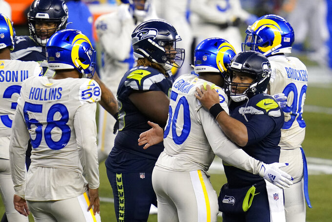 Seattle Seahawks quarterback Russell Wilson (3), second from right, greets Los Angeles Rams outside linebacker Samson Ebukam (50) after an NFL football game, Sunday, Dec. 27, 2020, in Seattle. The Seahawks won 20-9. (AP Photo/Elaine Thompson)