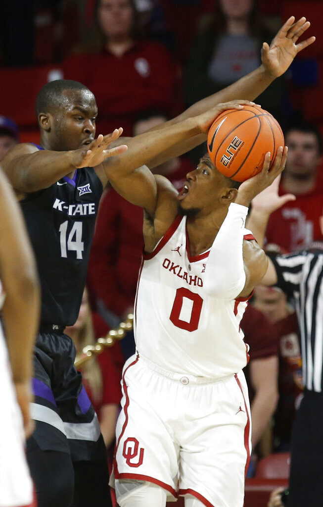 Kansas State forward Makol Mawien (14) defends as Oklahoma guard Christian James (0) looks for a shot during the first half of an NCAA college basketball game in Norman, Okla., Wednesday, Jan. 16, 2019. (AP Photo/Sue Ogrocki)