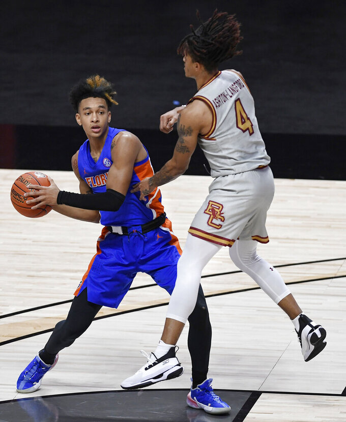 Florida's Tre Mann, left, looks to pass the ball as Boston College's Makai Ashton-Langford defends during the first half of an NCAA college basketball game Thursday, Dec. 3, 2020, in Uncasville, Conn. (AP Photo/Jessica Hill)