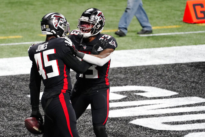 Atlanta Falcons linebacker Deion Jones (45) celebrates his touchdown with Atlanta Falcons cornerback Blidi Wreh-Wilson (33) against the Las Vegas Raiders during the second half of an NFL football game, Sunday, Nov. 29, 2020, in Atlanta. (AP Photo/Brynn Anderson)
