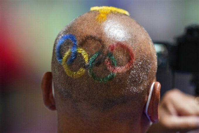 Mongolian coach Undralbat Lkhagva has the Olympic rings cut and dyed into his hair as he watches the women's 10-meter air pistol at the Asaka Shooting Range in the 2020 Summer Olympics, Sunday, July 25, 2021, in Tokyo, Japan. (AP Photo/Alex Brandon)