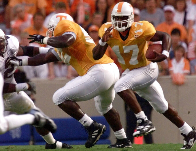 FILE - In this Sept. 4, 1999, file photo, Tennessee quarterback Tee Martin (17) runs through a hole made by teammate Cosey Coleman (52) during their 42-17 win over Wyoming in Knoxville, Tenn. Tennessee's wide receivers savor the opportunity to play for their new position coach because they appreciate what Tee Martin accomplished during his own playing career. Martin was the starting quarterback on Tennessee's 1998 national championship team and is back at his alma mater trying to help the Volunteers become competitive again in the Southeastern Conference. (AP Photo/Mark Humphrey, File)