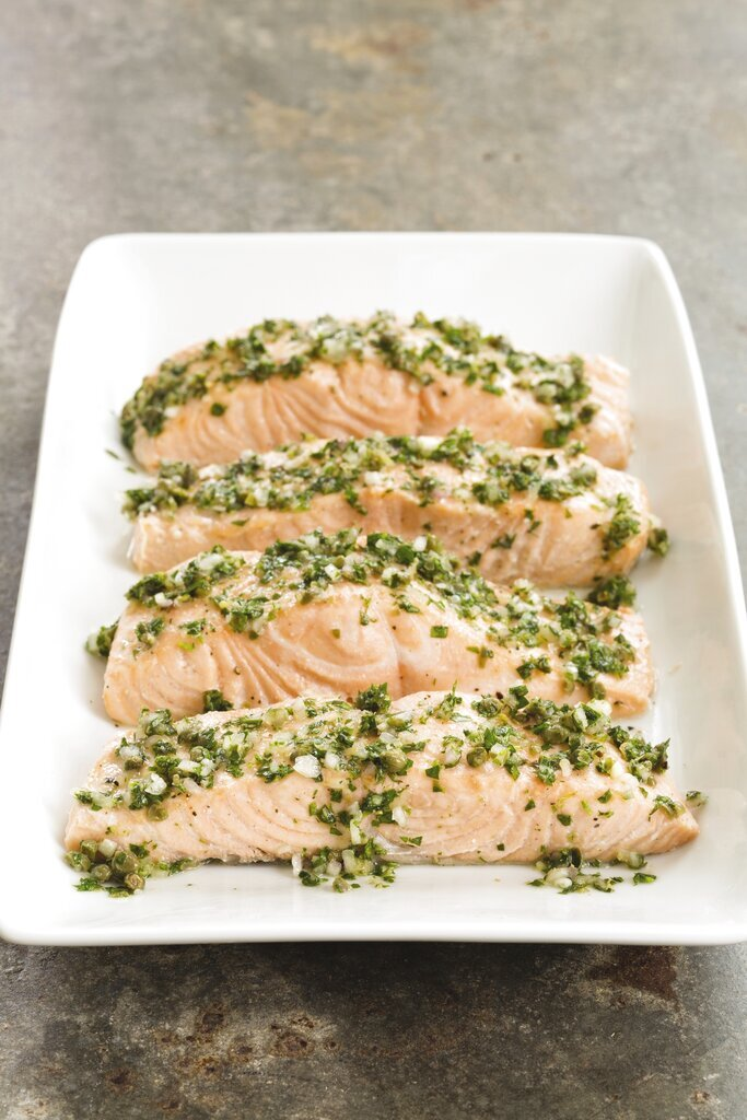 This undated photo provided by America's Test Kitchen in July 2019 shows Poached Salmon with Herb and Caper Vinaigrette in Brookline, Mass. This recipe appears in