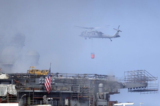 A helicopter approaches the USS Bonhomme Richard as crews fight the fire, Monday, July 13, 2020, in San Diego. Fire crews continue to battle the blaze Monday after 21 people suffered minor injuries in an explosion and fire Sunday on board the USS Bonhomme Richard at Naval Base San Diego. (AP Photo/Gregory Bull)