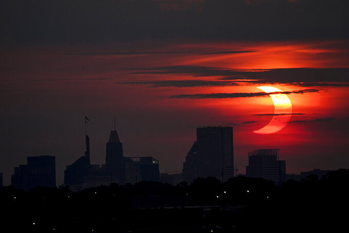 A partial solar eclipse rises over the Baltimore skyline, Thursday, June 10, 2021, seen from Arbutus, Md. (AP Photo/Julio Cortez)
