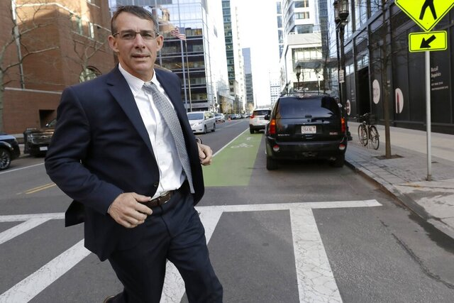 Michael Center, former men's tennis coach at the University of Texas at Austin, runs from federal court in Boston, Monday, Feb. 24, 2020, after being sentenced in a nationwide college admissions bribery scandal. (AP Photo/Steven Senne)