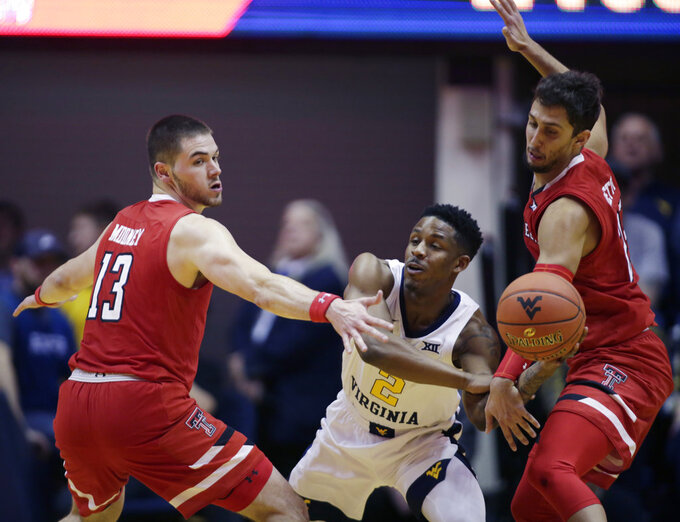 Texas Tech guard Matt Mooney (13) and guard Davide Moretti (25) trap West Virginia guard Brandon Knapper (2) during the second half of an NCAA college basketball game Wednesday, Jan. 2, 2019, in Morgantown, W.Va. Texas Tech defeated West Virginia 62-59. (AP Photo/Raymond Thompson)