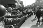 FILE - In this March 29, 1968, file photo, striking Memphis sanitation workers march past Tennessee National Guard troops with fixed bayonets during a 20-block march to City Hall in Memphis, Tenn. A national coalition of labor unions, along with racial and social justice organizations, will stage a mass walkout from work July 20, as part of an ongoing reckoning on systemic racism and police brutality in the U.S. The strike will continue a decades-old tradition of the American labor rights movement and most notably, organizers draw inspiration from the historic Memphis sanitation workers' strike. (AP Photo/Charlie Kelly, File)