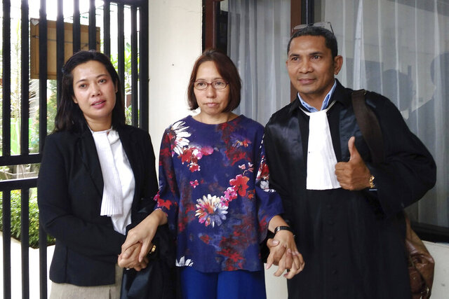 Suzethe Margareth, center, poses with her lawyers after her verdict at the Cibinong District Court in West Java, Indonesia, Wednesday, Feb. 5, 2020. Doctors say Marageth should receive psychiatric treatment as she is acquitted of blasphemy charges after taking a dog into a mosque. (AP Photo)