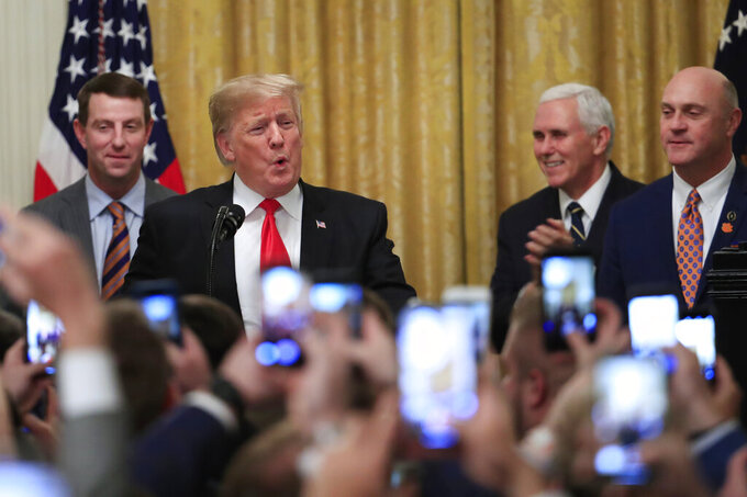 President Donald Trump joined by, from left, Clemson head coach Dabo Swinney, Vice President Mike Pence, and Clemson President James Clements, welcomes the 2018 college football playoff National Champion Clemson Tigers to the White House in Washington, Monday, Jan. 14, 2019. (AP Photo/Manuel Balce Ceneta)