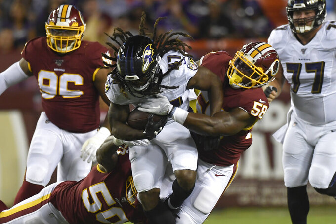 Washington Redskins linebacker Cassanova McKinzy (58) tries to strip the ball from Baltimore Ravens running back De'Lance Turner (47) during the first half of an NFL preseason football game at FedEx Field in Landover, Md., Thursday, Aug. 29, 2019. (AP Photo/Susan Walsh)