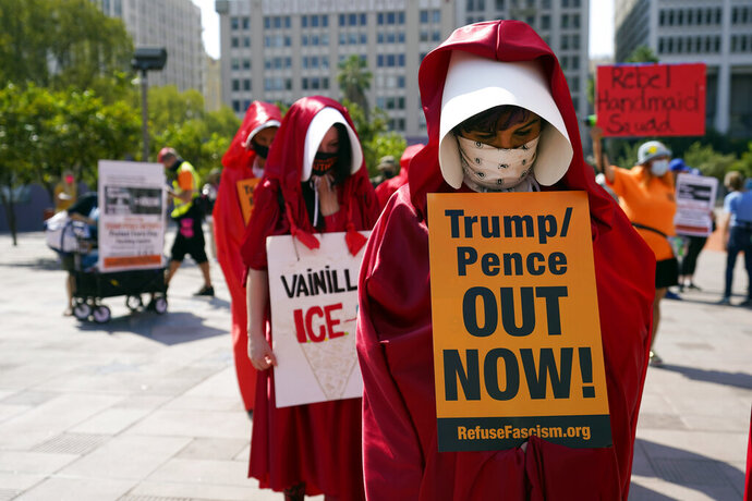 Demonstrators wear costumes and hold signs during a Women's March Saturday, Oct. 17, 2020, in Los Angeles. Thousands of women rallied in U.S. cities, to oppose President Donald Trump and his fellow Republican candidates in the Nov. 3 elections. (AP Photo/Marcio Jose Sanchez)