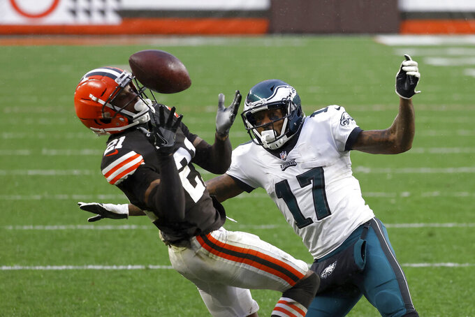 FILE - Cleveland Browns cornerback Denzel Ward (21) intercepts a pass intended for Philadelphia Eagles wide receiver Alshon Jeffery (17) during an NFL football game in Cleveland, in this Sunday, Nov. 22, 2020, file photo. The Cleveland Browns have exercised the fifth-year option on quarterback Baker Mayfield's rookie contract. The team also did the same with top cornerback Denzel Ward's contract. (AP Photo/Kirk Irwin, File)